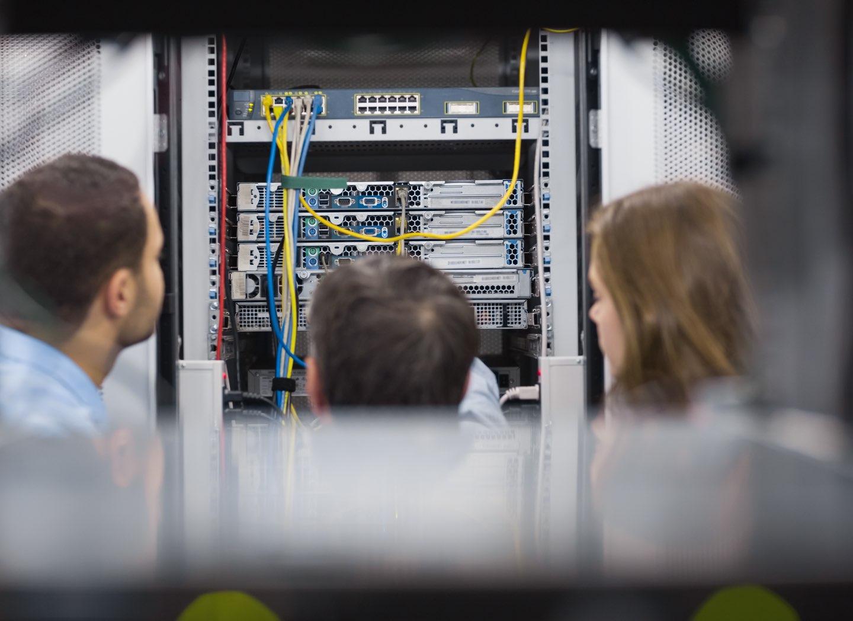 Tre personer kopplar in sladdar i en serverhall