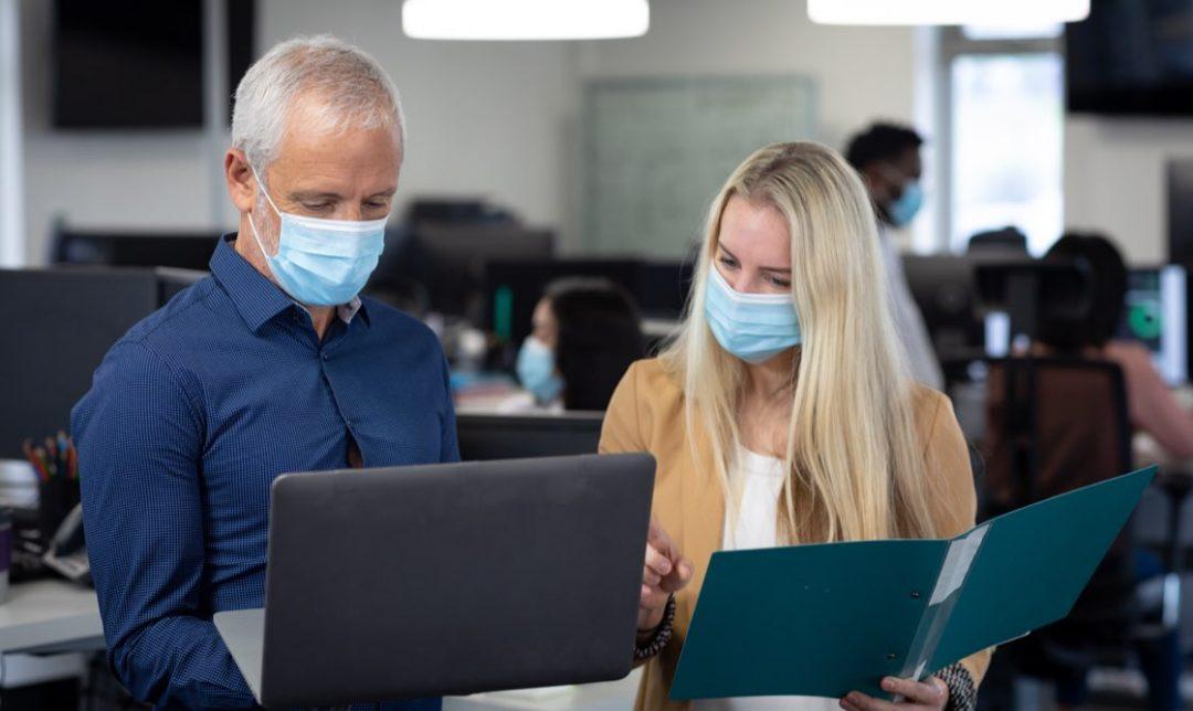 Man och kvinna med munskydd i kontorsmiljö