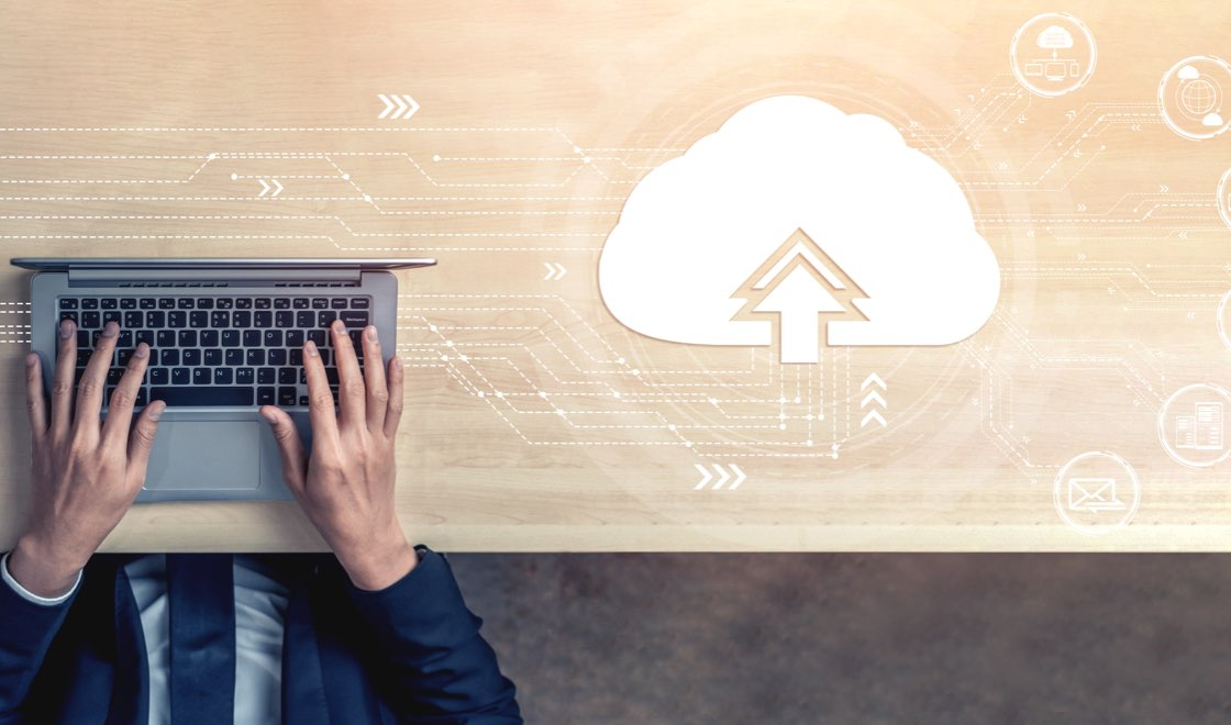 Händer på datortangenter till vänster, inklippt Cloud-märke till höger